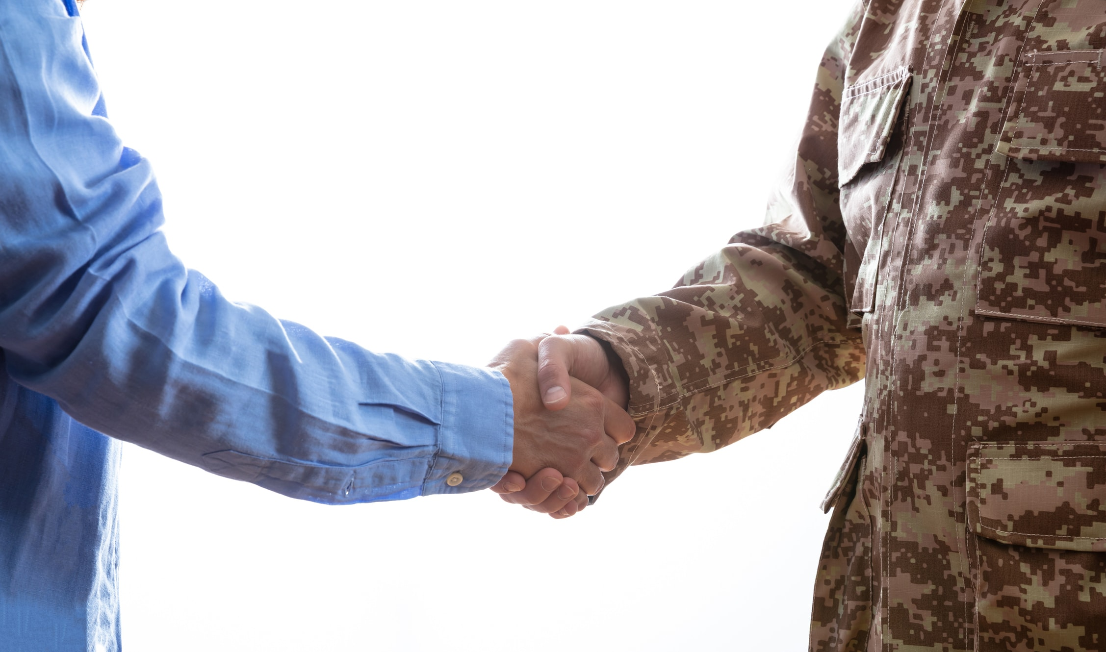 Military person and civilian shaking hands