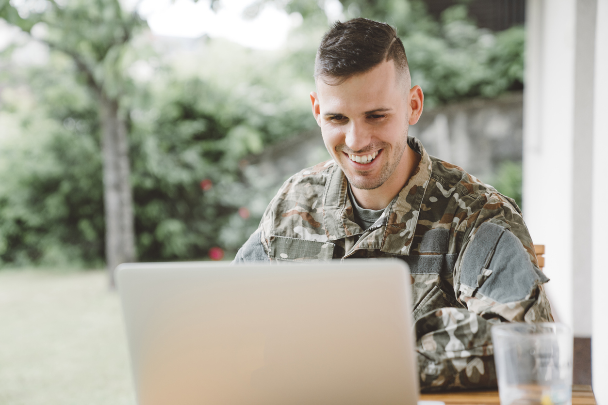 Smiling man in army uniform working on laptop