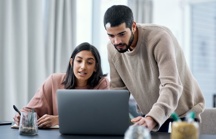 young man and woman using a laptop